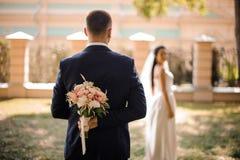 Brudgum i den stilfulla bröllopdräkten med en bukett av blommor arkivbilder