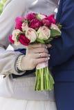 Brudgum i dräkt och brud i bröllopsklänning Arkivfoto