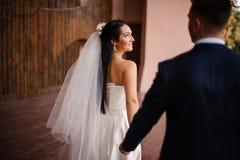 Brudgum i en blå dräkt som följer hans iklädda härliga le brud en vit klänning arkivfoto