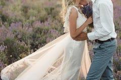 Brudgum i en vit skjorta och en brud i en klänning av vit färg i ett lavendelfält med en bukett av lavendel royaltyfri bild