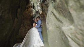 Brudgum med brudanseende i grotta av bergkullar Att gifta sig kopplar ihop förälskat stock video