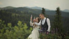 Brudgum med bruddrinkchampagne på kullar för ett berg binder crystal smycken f?r parcravaten br?llop familj stock video
