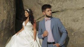 Brudgum med bruden nära bergkullar binder crystal smycken för parcravaten bröllop Förälskad lycklig familj lager videofilmer