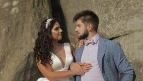 Brudgum med bruden nära bergkullar binder crystal smycken för parcravaten bröllop Förälskad lycklig familj stock video