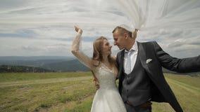 Brudgum med bruden som har gyckel på kullar för ett berg binder crystal smycken f?r parcravaten br?llop lycklig familj arkivfilmer