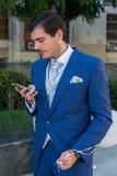 Brudgum med en telefon Arkivfoton