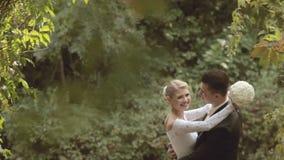 Brudgum och brud i en härlig klänning som in kysser arkivfilmer