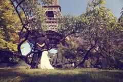Brudgum och brud i en parkera nära Eiffeltorn royaltyfria bilder