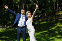 Brudgum och brud med händer upp Royaltyfria Bilder