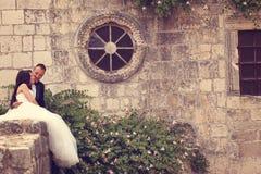 Brudgum och brud nära en gammal byggnad arkivbilder