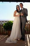 Brudgum och brud som rostar på en terrass som ler full längd Arkivfoton