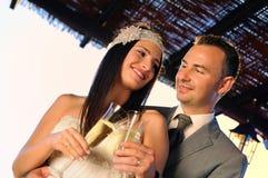 Brudgum och brud som rostar på en terrass som ler ögonkontakten Arkivbild
