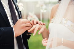 Brudgum och brud under bröllopceremoni, upp på händer som utbyter cirklar Gifta sig par och utomhus- bröllopceremoni Arkivbild