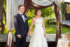 Brudgum och brud under dekorativ bröllopbåge Arkivfoton