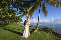Brudgum- och brudanseende vid palmträdet royaltyfria bilder