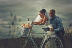 Brudgum och bruden med en cykel Royaltyfri Bild