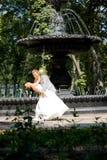 Brudgum- och brudglädje mot bakgrundspringbrunnen Arkivbilder