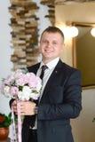 Brudgum på att gifta sig den le och väntande på bruden för smoking i korridoren av hotellet Rich ansar på bröllopdagen Elegant br royaltyfria bilder