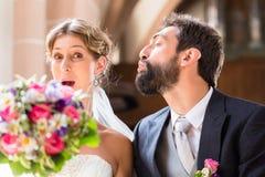 Brudgum som försöker att kyssa bruden i kyrka fotografering för bildbyråer