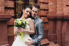 Brudgum som håller midjan av bruden Arkivbild