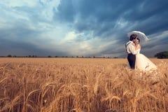 Brudgum som kysser bruden i vetefält Arkivbilder