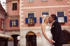 Brudgum som kysser hans brud i gammal stad Royaltyfria Foton