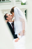 Brudgum som omfamnar brud- och kyssnäsan. Förälskelsepar Arkivfoton