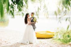 Brudgum som omfamnar bruden nära fartyget Royaltyfria Foton