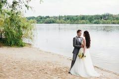 Brudgum som omfamnar bruden på flodbanken Arkivbild