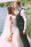 Brudgum som omfamnar den sinnliga bruden nära dammet Royaltyfri Foto