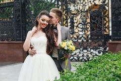 Brudgum som omfamnar hans eleganta brud Fotografering för Bildbyråer