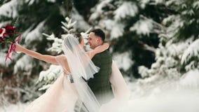 Brudgum som rotera den lyckliga bruden som rymmer och rotera henne i hans händer i skog för träd för snövädergran prydlig under s