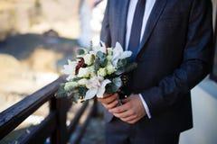 Brudgum som rymmer den brud- buketten Royaltyfria Bilder