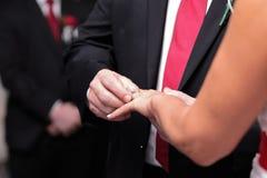 Brudgum som sätter cirkeln på bruds finger på en gifta sig ceremoni royaltyfri fotografi