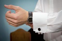 Brudgum som sätter på hans cufflinks Royaltyfri Fotografi