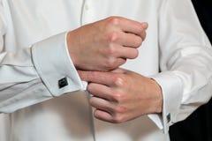 Brudgum som sätter på hans cufflinks Arkivfoto