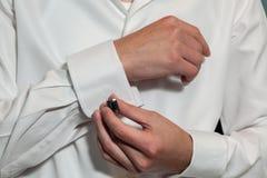 Brudgum som sätter på hans cufflinks Fotografering för Bildbyråer