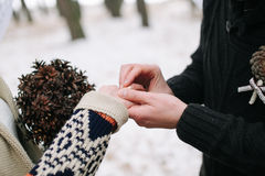 Brudgum som sätter vigselringen på brudfingret Arkivfoto