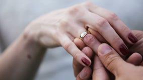 Brudgum som sätter vigselringen på brudfingret lager videofilmer