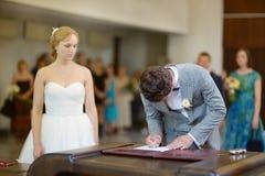 Brudgum som undertecknar ett bröllopavtal Arkivfoton