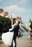 Brudgum som vänder hans brud på vägen Arkivfoton