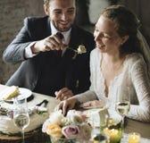 BrudgumFeeding Cake To brud på bröllopmottagande arkivbild