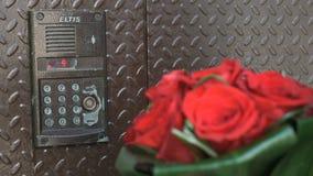 Brudgumhåll i en hand en bukett av röda rosor lager videofilmer