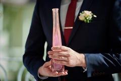 Brudgumhållflaska med rosa färgsand på bröllop arkivbilder