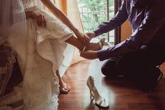 Brudgumhjälp som bär brud- skor Fotografering för Bildbyråer