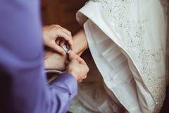 Brudgumhjälp som bär brud- skor Royaltyfri Fotografi
