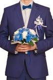 Brudgumkostnaderna med en bukett på blommor för bruden Royaltyfri Fotografi