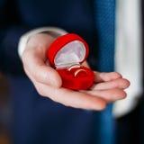 BrudgumMan Holding Holding ask med vigselringar Arkivfoton