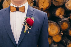 Brudgummar med träflugan och röd rosboutonniere på trä Arkivbilder