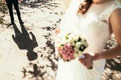 Brudgummar skuggar nästan bruden med bröllopbuketten Royaltyfri Foto